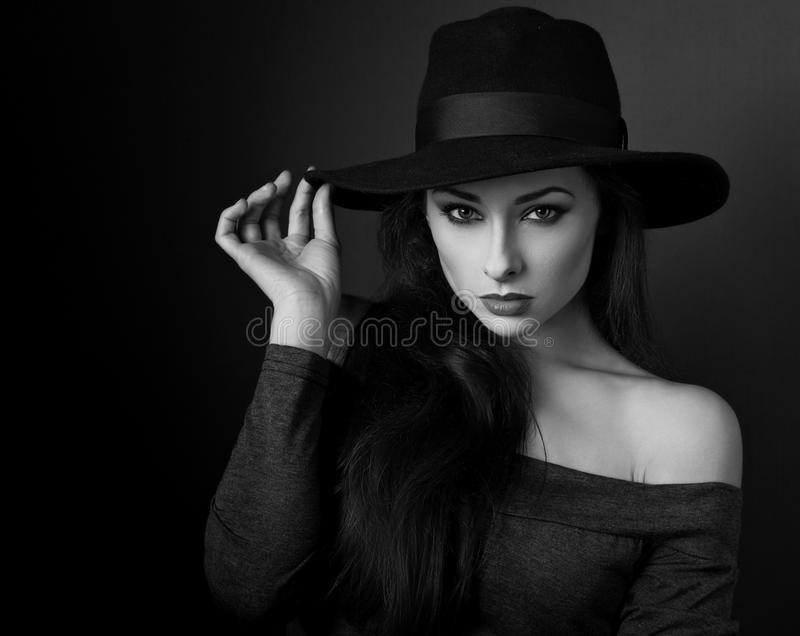 Elegante make-upvrouw in manierhoed het stellen op donkere schaduw backgr royalty-vrije stock foto