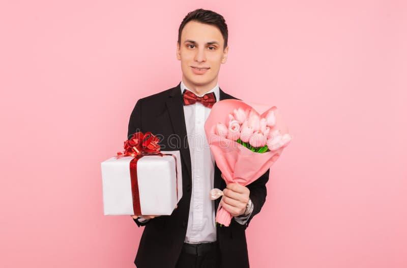 Elegante man, in een kostuum, met een boeket van bloemen, en een giftdoos, op een roze achtergrond, het concept de dag van vrouwe royalty-vrije stock foto