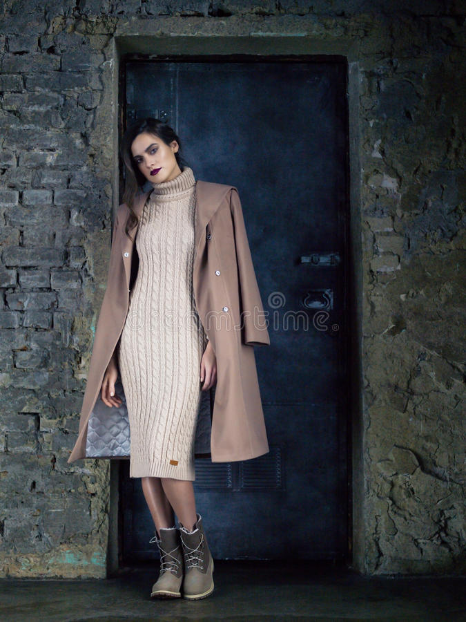 Elegante mannequin die lange mochalaag dragen, die vóór een deur stellen stock fotografie