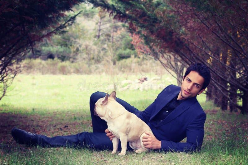 Elegante mens die daarna zijn hond zitten stock afbeeldingen