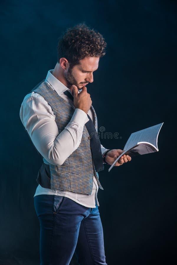Elegante mens die een boek in studioschot lezen stock fotografie