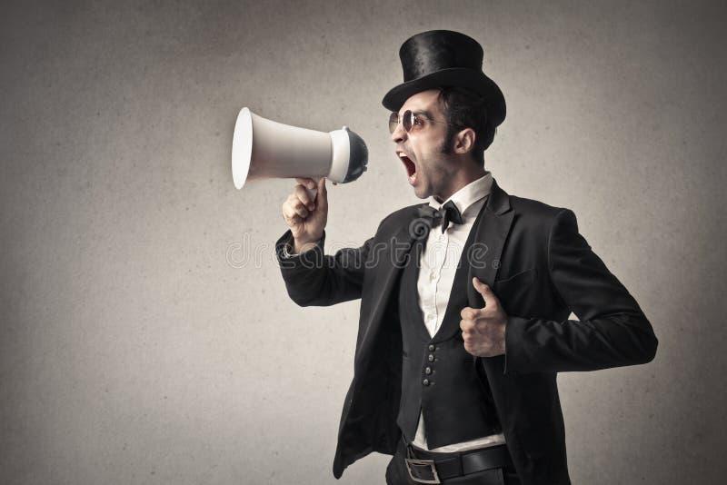 Elegante mens die in een megafoon gillen royalty-vrije stock afbeeldingen