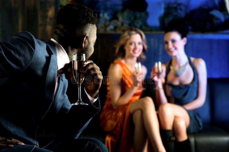 Elegante mens die hete jonge meisjes in nachtclub bekijken royalty-vrije stock foto