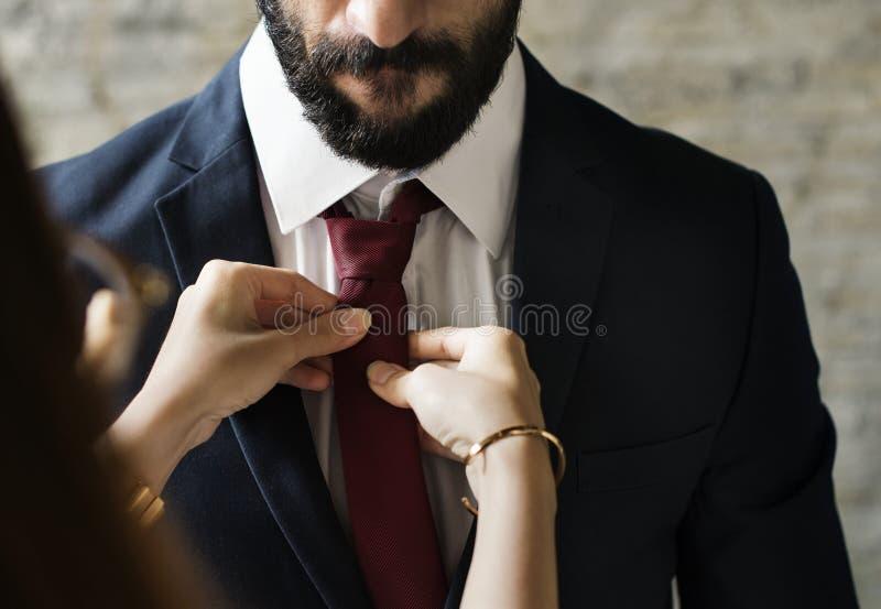 Elegante mens die omhoog door zijn vrouw worden gekleed stock foto's