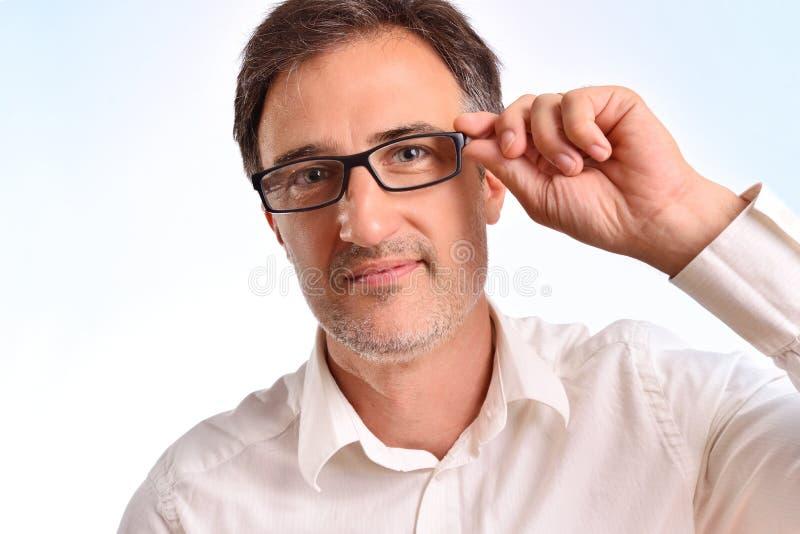 Elegante mens die op middelbare leeftijd met wit overhemd de glazen aanpassen stock foto