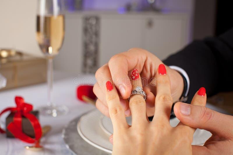 Elegante mens die verlovingsring zetten aan zijn meisjehand stock afbeeldingen