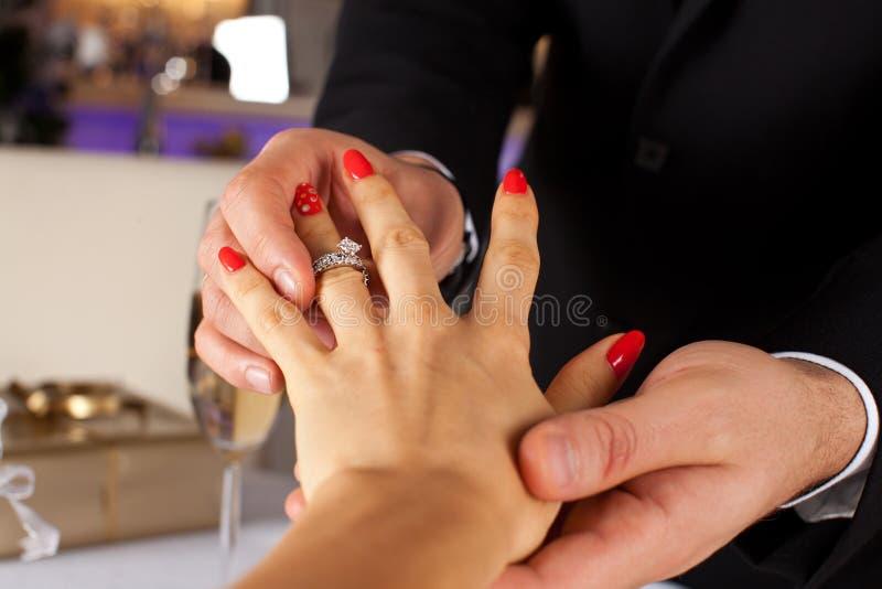 Elegante mens die verlovingsring zetten aan zijn meisjehand royalty-vrije stock fotografie