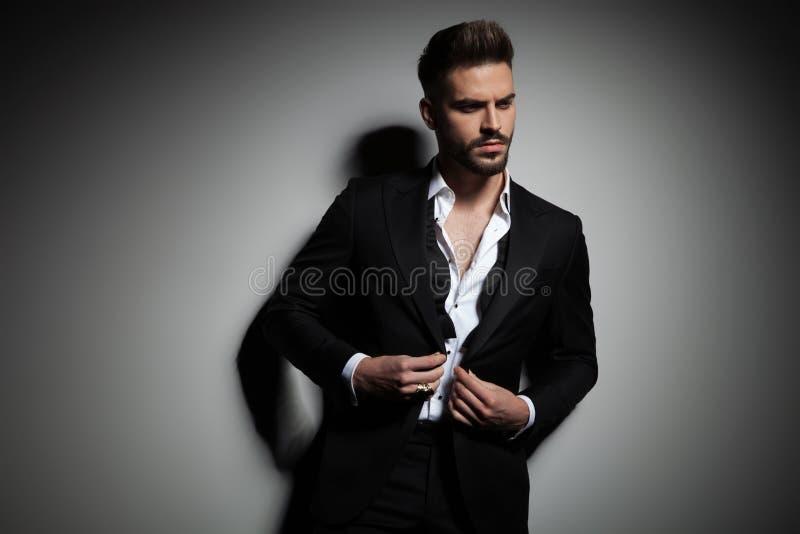 Elegante mens die in zwarte smoking zijn kostuum dichtknopen stock fotografie