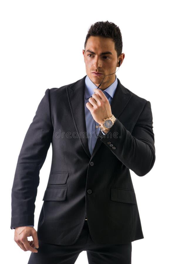 Elegante mens met oortelefoons, een veiligheidspersoneel stock fotografie