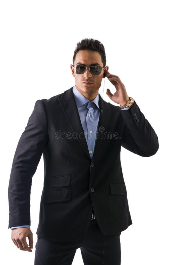 Elegante mens met oortelefoons, een veiligheidspersoneel stock foto