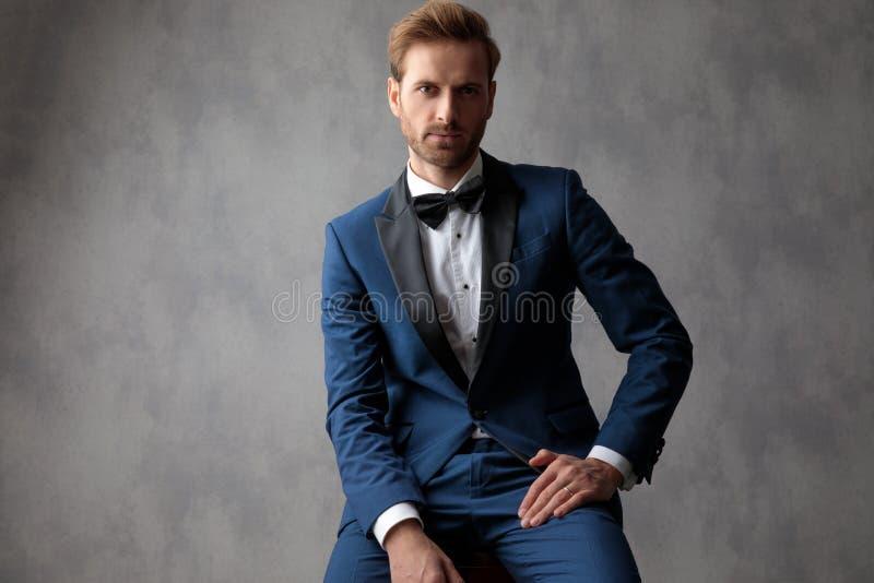 Elegante mensenzitting, holding een hand op zijn been stock foto