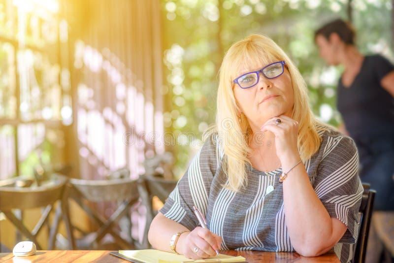 Elegante Mitte des Porträts, die plus Größenfrauensitzen gealtert wird und Anmerkungen zu ihrem Tagebuch auf Balkon oder Terrasse lizenzfreies stockfoto