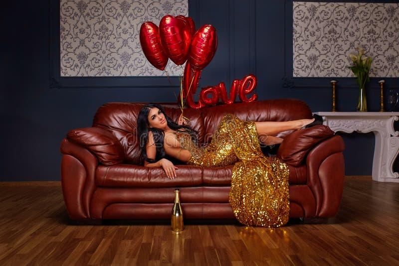 Elegante moderne Dame in einem goldenen sexy Kleid, das auf einem luxuriösen modernen Sofa gegen den Hintergrund in einem grauen  lizenzfreie stockfotografie