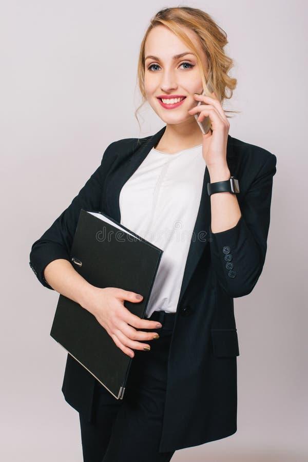 Elegante moderne junge Bürofrau in der Klage, Holdingordner, sprechend am Telefon lokalisiert auf weißem Hintergrund freundlich lizenzfreie stockfotografie