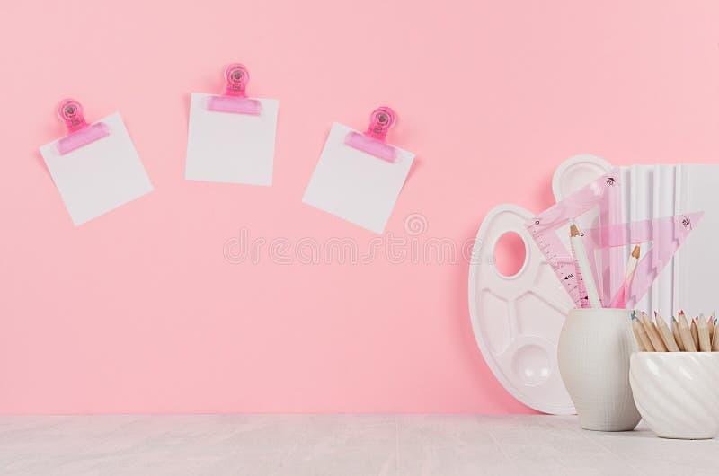 Elegante moderne ontwerperswerkplaats met witte kantoorbehoeften, palet, potloden, stickers op roze achtergrond royalty-vrije stock afbeelding