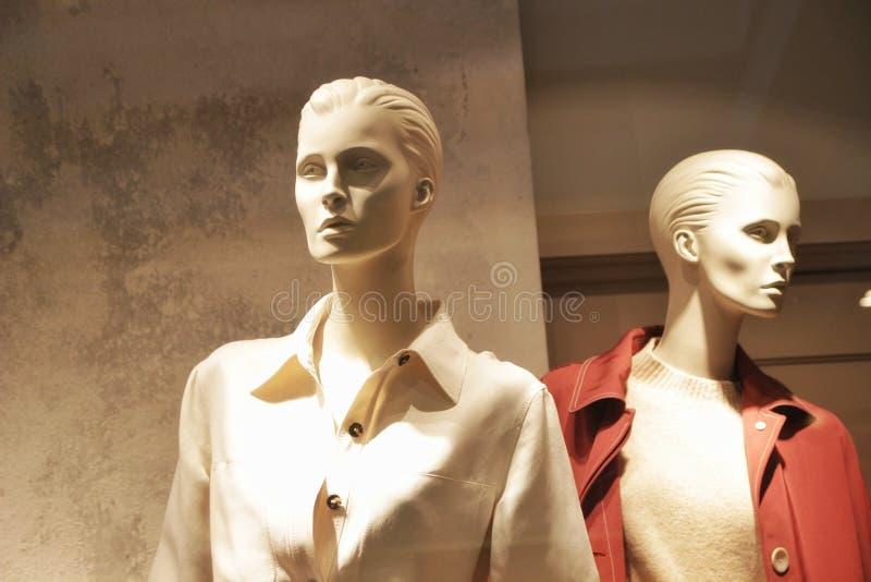 Elegante moderne vrouwelijke ledenpoppen in de showcase van een kledingsopslag, warme gamma royalty-vrije stock afbeeldingen