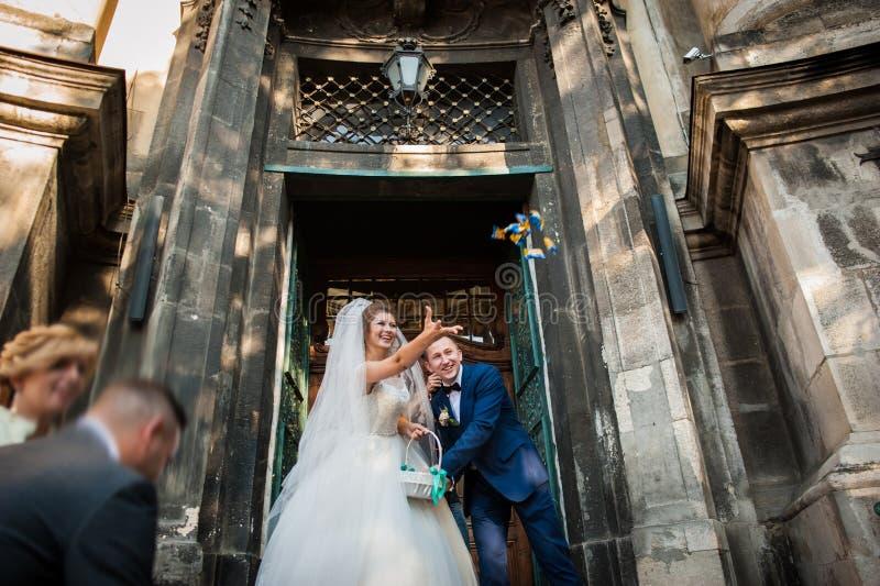 Elegante modieuze bruidegom met zijn gelukkige schitterende donkerbruine bruid  stock afbeeldingen