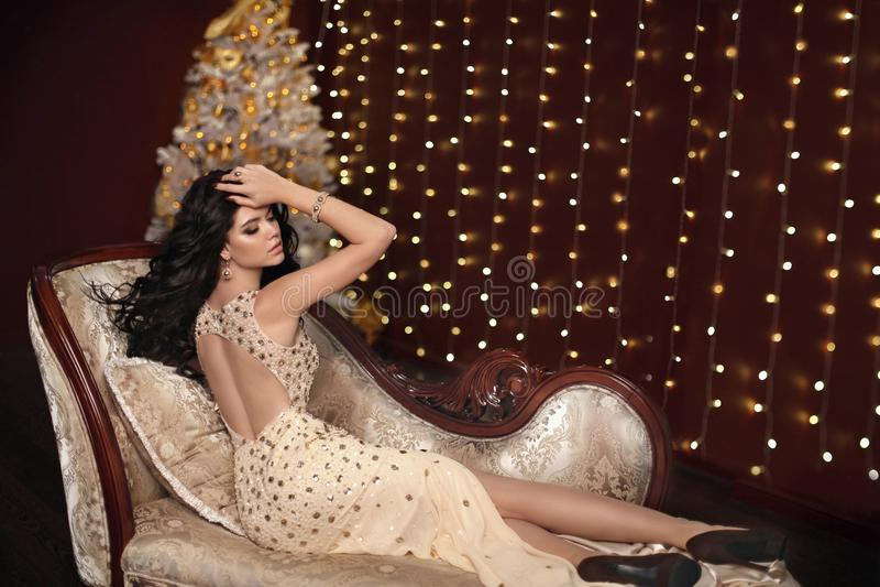 Elegante modieuze dame in gouden sexy kleding die op luxueuze moderne bank over Kerstmisachtergrond liggen stock fotografie