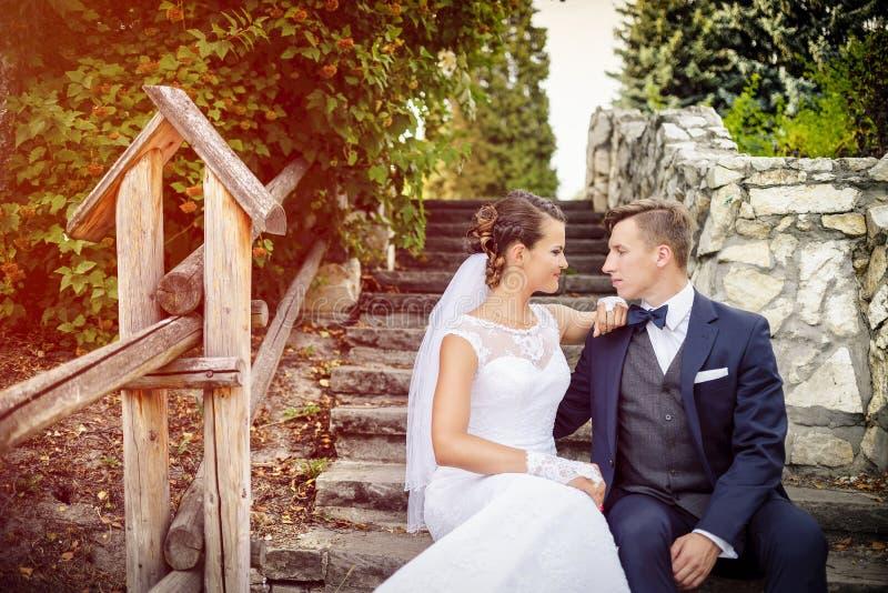 Elegante modieuze jonge bruid en bruidegomzitting op de treden in het park stock foto