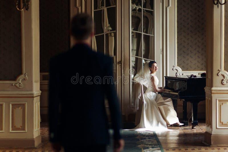 Elegante modieuze knappe bruidegom die zijn schitterende bruidpla bekijken royalty-vrije stock afbeeldingen