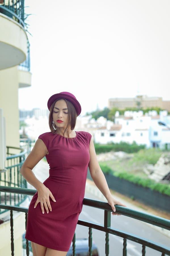 Elegante mooie jonge dame die zich op balkon, portret bevinden royalty-vrije stock afbeeldingen