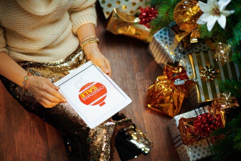 Elegante mujer de 40 años recibió cupón en la tablet PC imagen de archivo libre de regalías