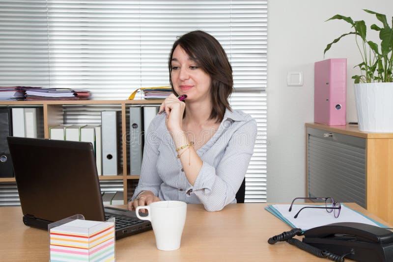elegante onderneemster met laptop in een helder bureau royalty-vrije stock afbeelding
