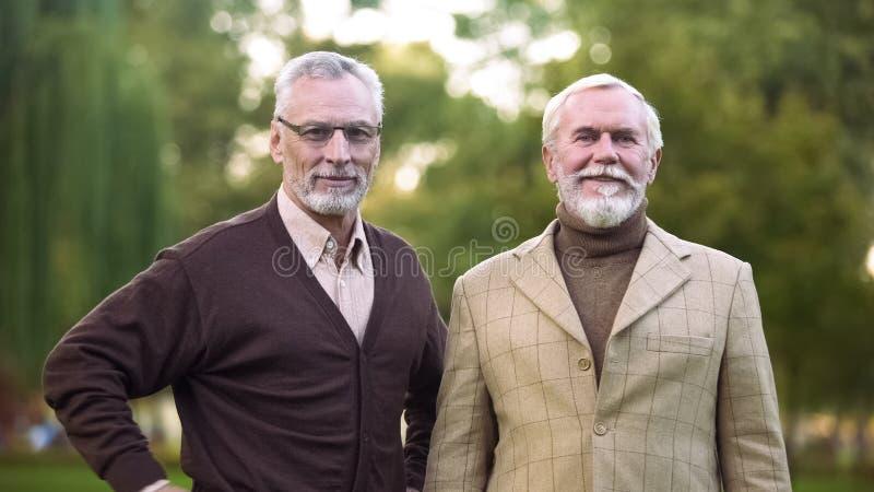 Elegante oude mensen die camera en het glimlachen, gelukkige pensionering, succes en rijkdom kijken stock afbeelding