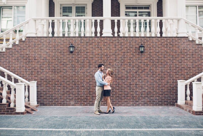 Elegante Paare, die auf Königshaus mit Backsteinmauer und weißem Treppenhintergrund umarmen Sie reizend miteinander schauend lizenzfreies stockfoto