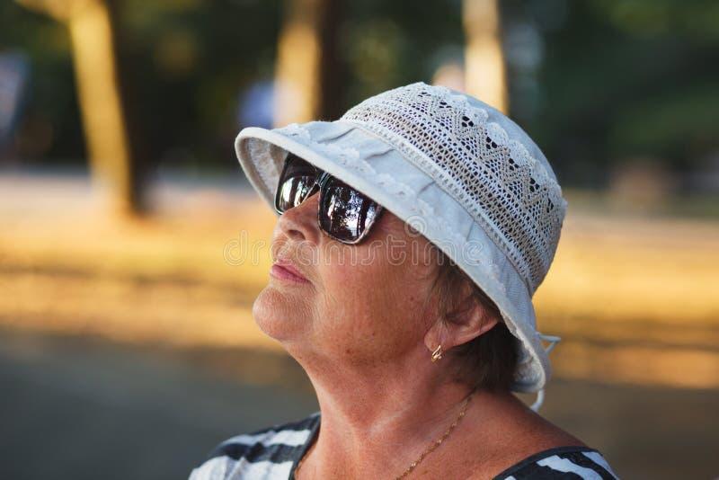 Elegante reife Frau, die Sommersonnenuntergang im Park genießt lizenzfreie stockbilder