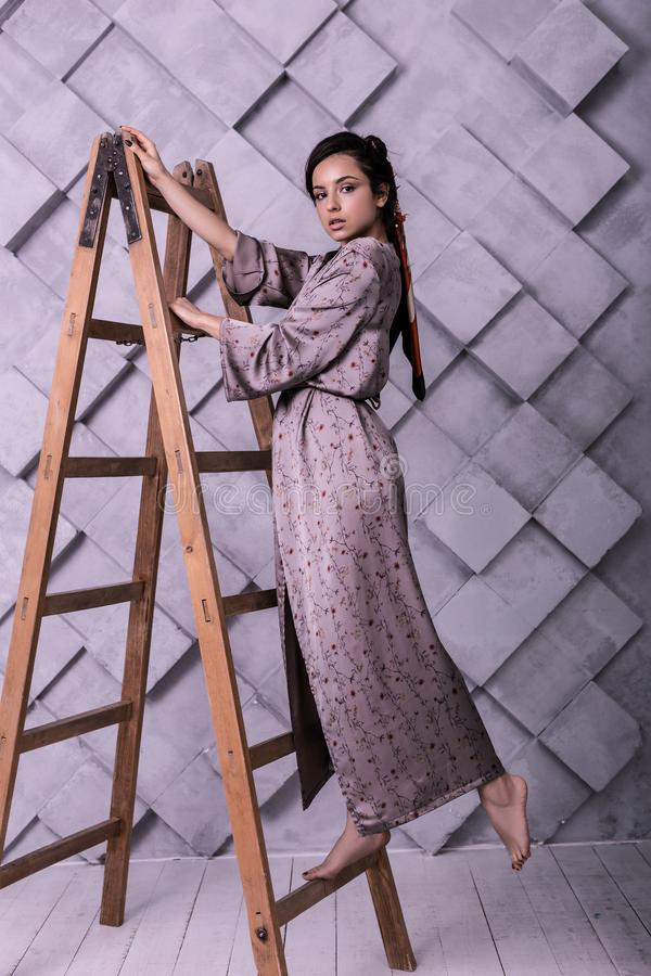 Elegante reizend Frau, die liebenswürdig Haltungen während des Studioschießens tut stockbild