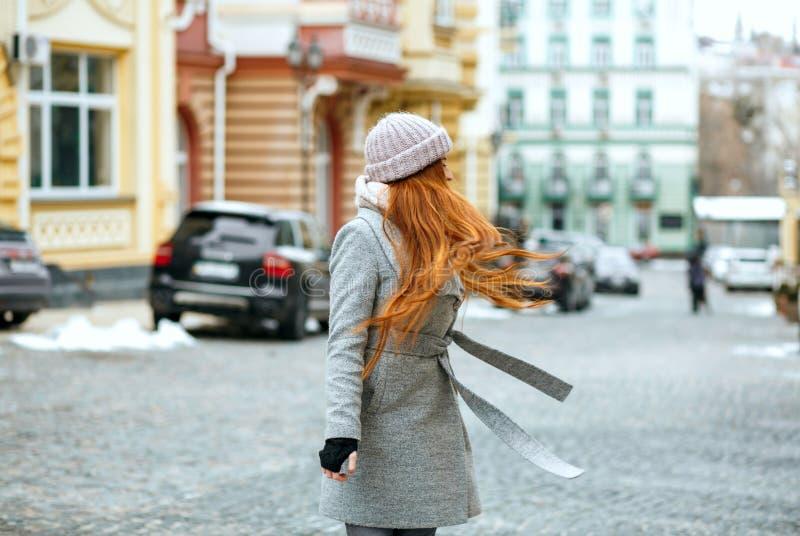 Elegante roodharigevrouw die modieuze de winteruitrusting dragen die binnen lopen royalty-vrije stock fotografie