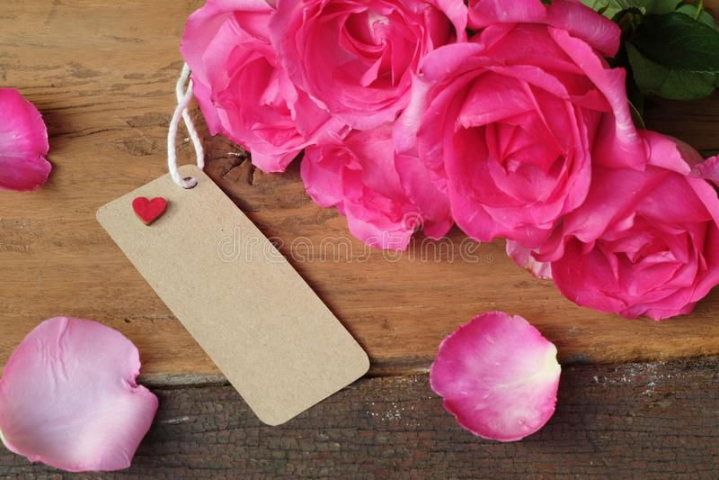 Elegante rosa Rose, Geschenkbox verziert mit den Blumenblättern und Karte mit natürlichem weichem Licht auf hölzernem Hintergrund lizenzfreies stockbild