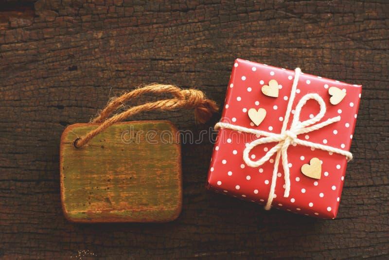 Elegante rote Geschenkbox und hölzerner Umbau auf hölzernem Hintergrund, anwesendes Konzept der Valentinsgrußliebe lizenzfreie stockbilder