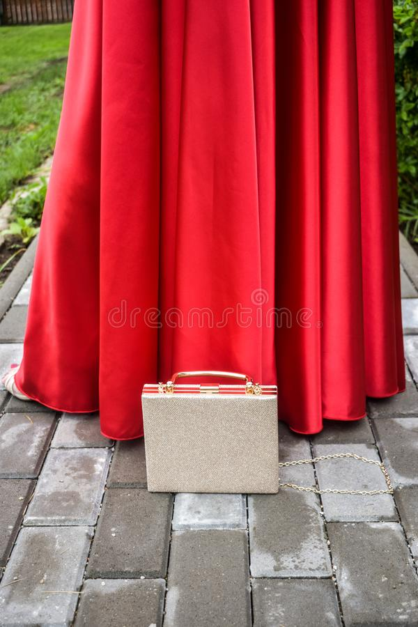 Elegante rote Kleiderdame mit stilvollem Luxusgeldbeutel auf dem Pflasterungsbürgersteig, der wartet, um am Ereignis zu gehen lizenzfreies stockbild