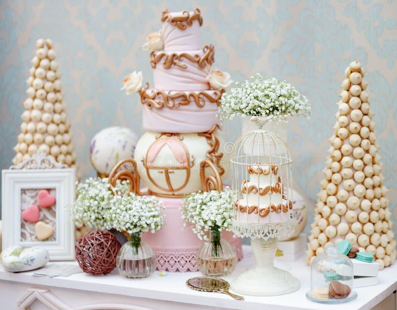 Elegante süße Tabelle mit großem Kuchen und Makrone lizenzfreie stockbilder
