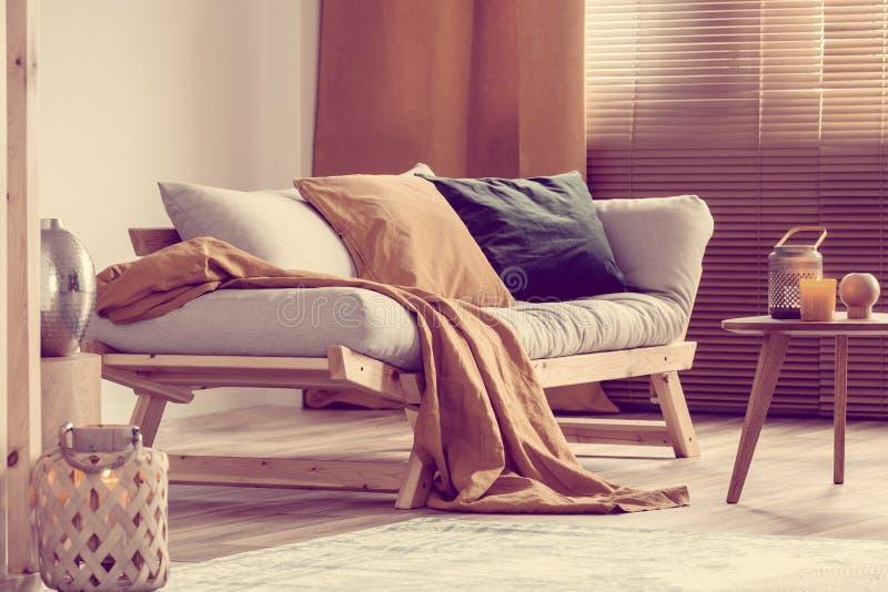 Elegante salón natural con muebles de madera en bruto y acentos naranjas fotos de archivo