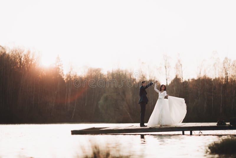 Elegante schöne Hochzeitspaare, die nahe einem See bei Sonnenuntergang aufwerfen stockfoto