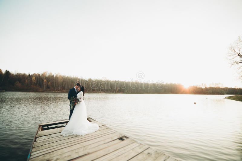 Elegante schöne Hochzeitspaare, die nahe einem See bei Sonnenuntergang aufwerfen lizenzfreies stockbild