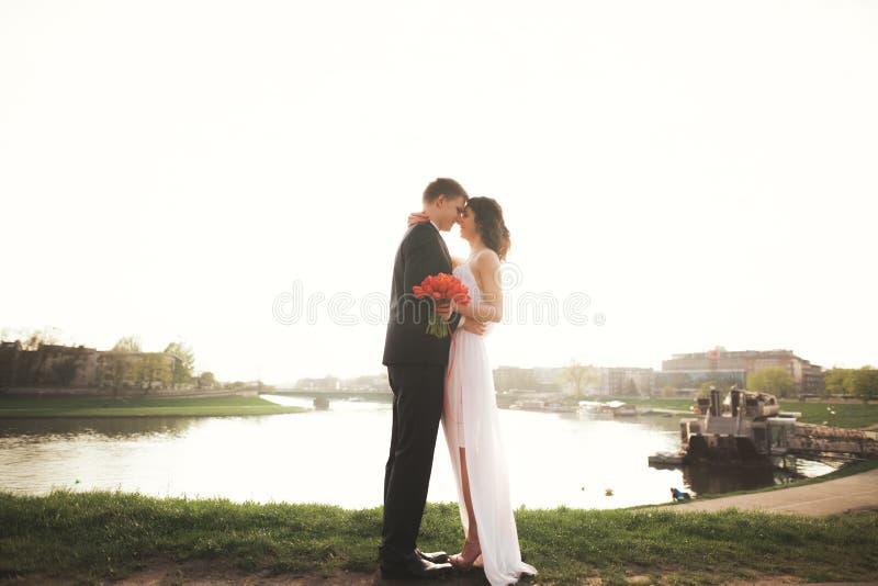 Elegante schöne Hochzeitspaare, die nahe Fluss bei Sonnenuntergang aufwerfen lizenzfreie stockbilder