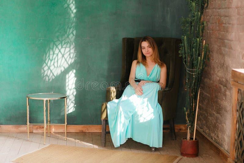 Elegante Schönheit, die das klassische Kleid sitzt im Dachbodeninnenraum mit Bretterboden und Backsteinmauer trägt Große Grüne le lizenzfreie stockfotografie