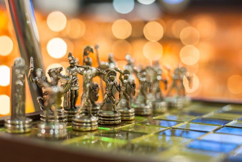 Elegante schackbräde med mässingsschackpjäser - foto med selektivt royaltyfria bilder