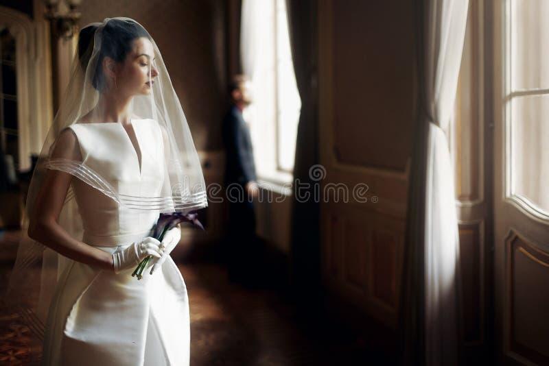 Elegante schitterende bruid die zacht onder sluier modieuze groo bekijken royalty-vrije stock foto's