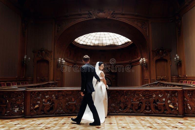 Elegante schitterende bruid en het modieuze bruidegom stellen bij oude houten st stock foto
