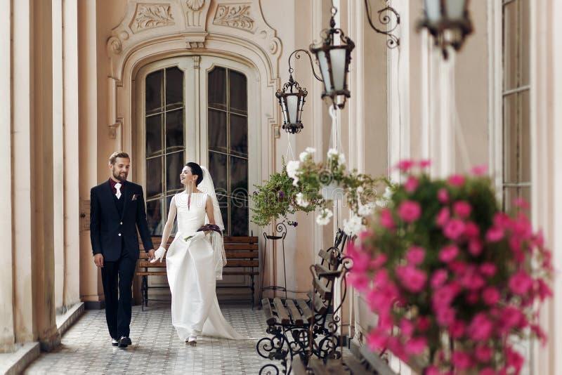 Elegante schitterende bruid en modieuze bruidegom het lopen holdingshanden, stock foto's