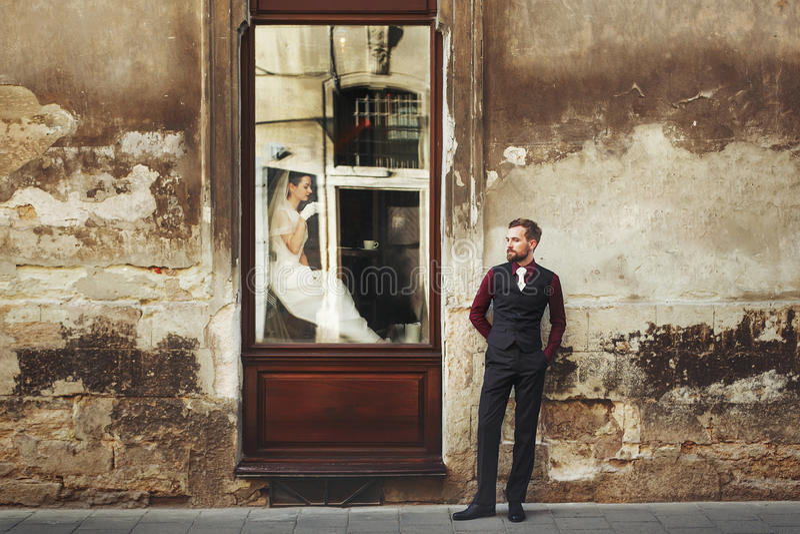 Elegante schitterende bruid het drinken koffie in venster en modieuze gr. royalty-vrije stock foto's