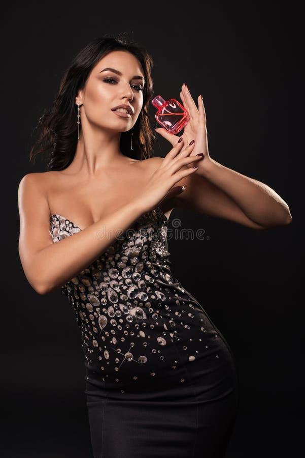 Elegante schoonheidsvrouw in een mooie kleding met parfum op donkere achtergrond stock foto