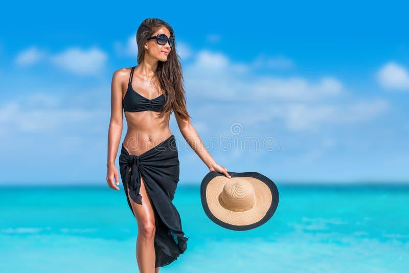 Elegante schwarze Bikinifrau mit Hutsonnenbrille stockfotos