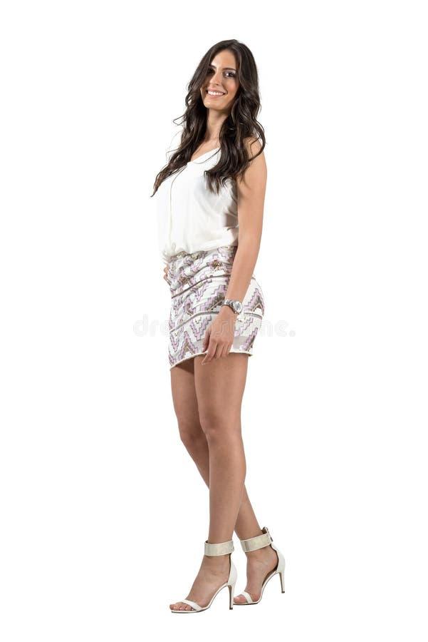 Elegante sensuele lange golvende haarschoonheid in korte kleding die bij camera glimlachen stock foto's