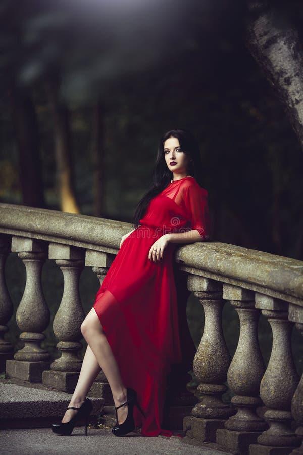 Elegante sensuele sexy jonge vrouw in het rode kleding stellen dichtbij een leuning stock foto's